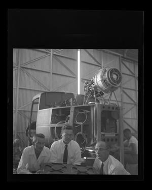 Primary view of object titled '[Bell employees posing in front of an unfinished fuselage of an XH-40]'.
