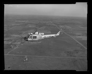 Primary view of object titled '[XH-40 number 3 in first flight over Hurst plant]'.