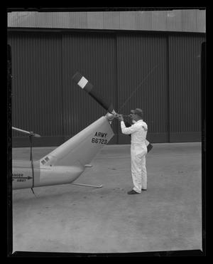 Primary view of object titled '[Service man performing maintenance on tail rotor of the YH-40]'.
