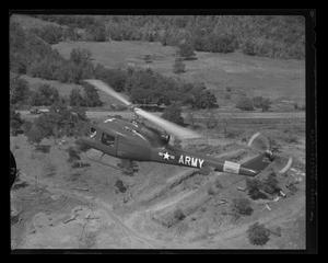 Primary view of object titled '[YH-40 #7 in Olive Drab paint, flying over a field]'.