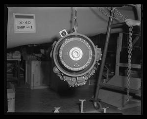 Primary view of object titled '[The Lycoming turbine engine being hoisted to the top of XH-40 #1]'.