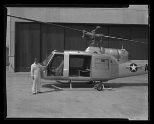 Primary view of object titled '[Bell employee holding the door open to the YH-40 helicopter]'.