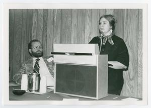 Primary view of object titled '[Woman Speaking at Podium with Recording Device]'.
