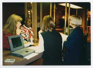 Primary view of object titled '[Four People Standing at a Reception Desk]'.