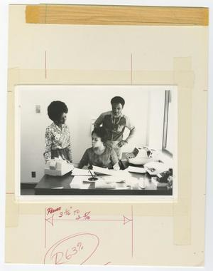 Primary view of object titled '[Three Unidentified People Working at a Desk]'.