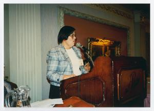 Primary view of object titled '[Woman Standing and Giving Speech at Podium]'.