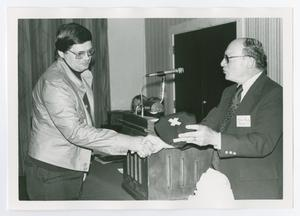 Primary view of object titled '[Two Men Shaking Hands and Exchanging a Plaque]'.