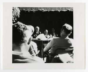 Primary view of object titled '[Men Sitting at a Table Talking to a Group]'.