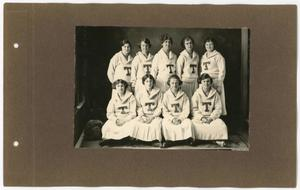 A brown yearbook page with a black and white photo on it. The photo is of a group of 9 women, 4 in a row sitting at the front, 5 women standing behind them. They all have skirts and white sweaters with a big T on it.
