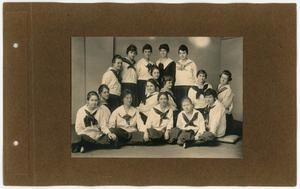 The right side of an open scrapbook page, brown in color. On the page is a black and white photo of a group of people in 3 rows, posing for a picture. They are wearing white shirts with an eagle on it.