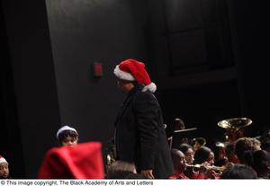 Primary view of object titled '[Unidentified Conductor on Stage Wearing Christmas Hat]'.