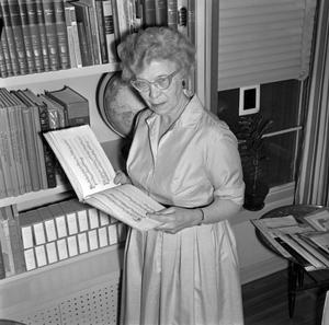 Primary view of object titled '[Dr. Helen Hewitt, reading sheet music]'.