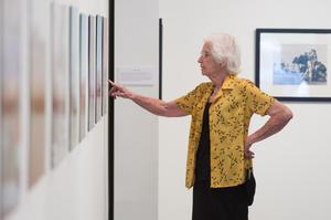 A woman in a yellow shirt touches the wall in front of her with her right hand. The wall holds photographs.