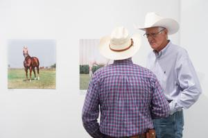 A man is seen from behind in a plaid shirt and cowwboy hat. In front of him, a man in a cowboy hat is seen from the front talking to the other man. Photos of horses are seen behind them.