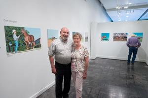 A man and women with white hair stand next to each other. By them on a wall are pictures of a gallery of cowboys and horses.