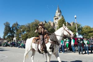 Primary view of object titled '[Cowgirl Riding Horse in the UNT Homecoming Parade]'.