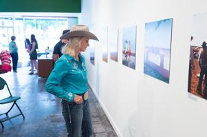 A woman with blonde hair and wearing a blue shirt and cowboy hat stands in front of a wall, facing the photos on it. Behind her other people walking around can be seen.