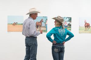 A man in a cowboy hat stands by a woman to his right, also in a cowboy hat and wearing a blue shirt. They are seen from the back facing a wall of photographs.