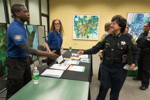 Primary view of object titled '[Police officers shake student's hand the LGBTQIA Career Fair, 1]'.
