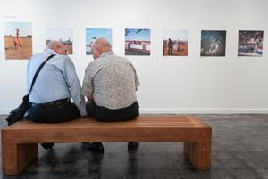 2 older men sit on a brown bench. The man on the left wears a bag around him. They are seen from the back, with a wall of photos directly in front of them.