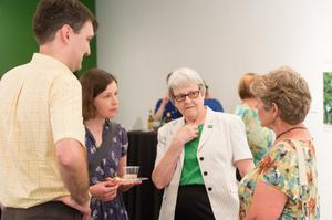 Four people stand around each other in conversation. The two women on the right are a bit older. The man on the left is in a light yellow shirt. The  second woman from the right has on a green shirt.