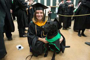 Primary view of object titled '[Graduating Student Poses with Dog for Photo]'.