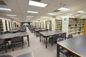 Color photograph of an aisle between book cases, with two rows of black tables and chairs leading towards and arched window on the back wall.