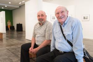 Two men sit by each other in an art gallery, smiling at the camera. The  man on the farthest right is older, with tubes coming out of his nose.