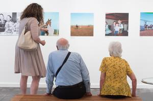 The back of three people are seen. One is an older woman on the farthest right sitting down in a yellow shirt. Next to her to the left is an old man in a blue shirt, also sitting down. To the farthest left is a younger woman in a dress. They are all looking at a wall with photographs on it.