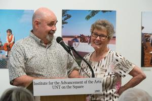A man and older woman stand behind a podium with a wall of photos behind them. The podium says Institute for the Advancement of the Arts.