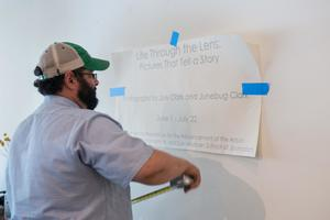 Primary view of object titled '[Man adding exhibit text to gallery wall]'.