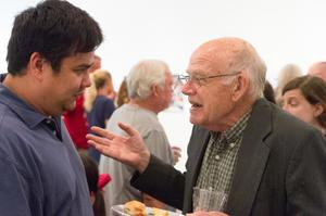 A man in a blue shirt talks to an older man in front of them, who is holding a plate and a cup. This photo is from a side view.