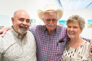 Three people stand next to each other, one being an older woman on the right. The man in the middle wears a cowboy hat and has his arms around the two people next to him.