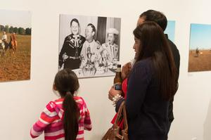 A young girl in pink with her hair pulled back stands next to a woman and man to her right. They are all seen from the back, looking at photos on the wall.