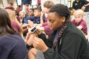 Primary view of object titled '[Westlake Academy Charter School student looks at microfilm]'.