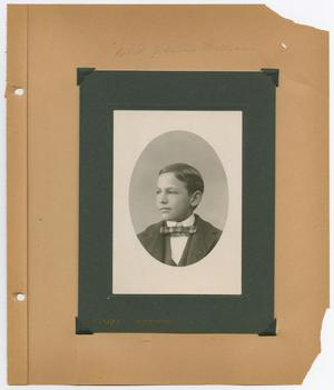 The right side of an open book is seen, showing a black and white photo of a young boy in a suit and bow tie.