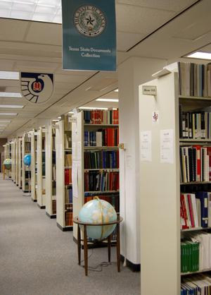 Color photograph looking down an aisle with many rows of bookshelves and three globes. A sign hanging from the ceiling reads Texas State Documents Collection.