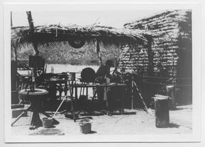 Person Working Under Small Structure With Thatched Roof