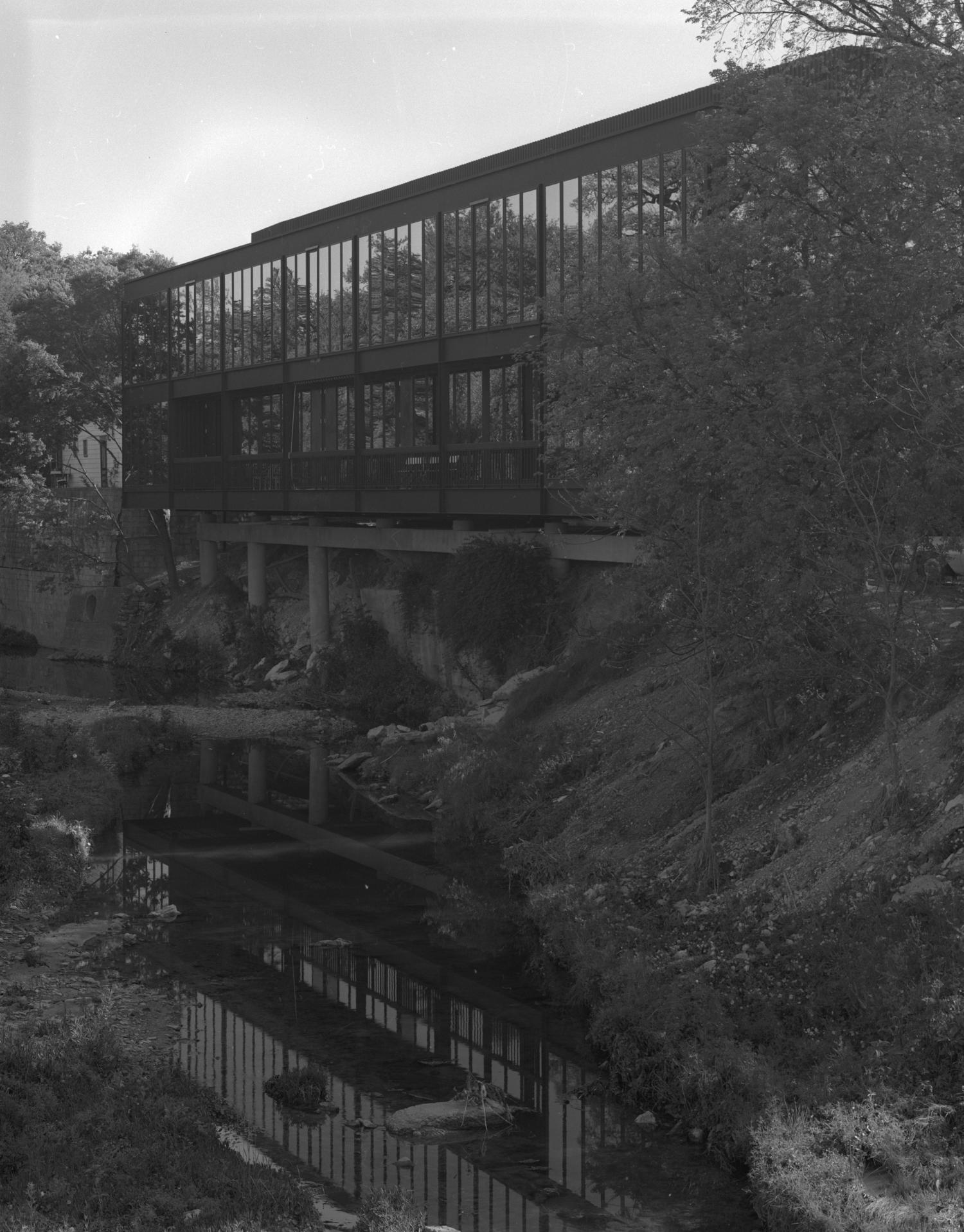 [Mirrored Building], Photograph of a dark, mirrored, postmodern building poised on a ledge. The windows are highly reflective and a balcony can be seen overlooking a creek to the left. Trees and other foliage can be seen throughout the area and a light colored building can be partially seen in the background to the left.,
