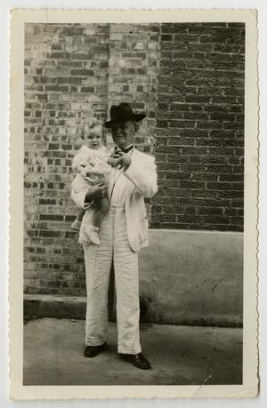 [Photograph of a man holding a baby]