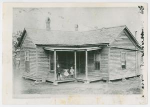 [Photograph of three children on the porch of a wooden house]