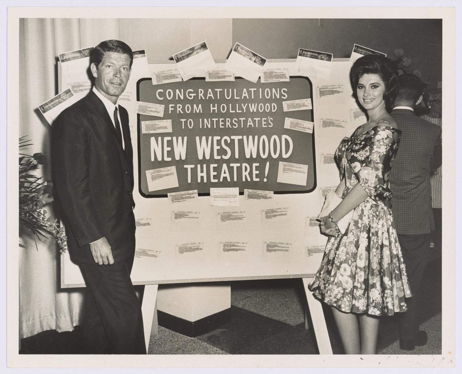 [Stephen Boyd and Beverly Adams at grand opening of Westwood Theatre], Photograph of actors Stephen Boyd and Beverly Adams at a publicity event for the grand opening of the Westwood Theatre in Richardson, Texas. Boyd and Adams pose in front of a poster covered in Western Union telegrams from Hollywood.,