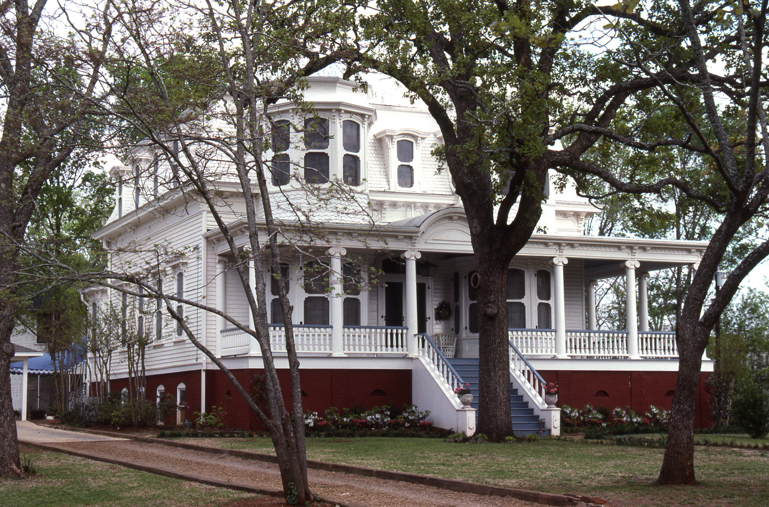 [412 S. Royall], Close-up photograph of the northwest corner of a two-story white house with blue and red accents, located at 416 S. Royall in Palestine, Texas.,