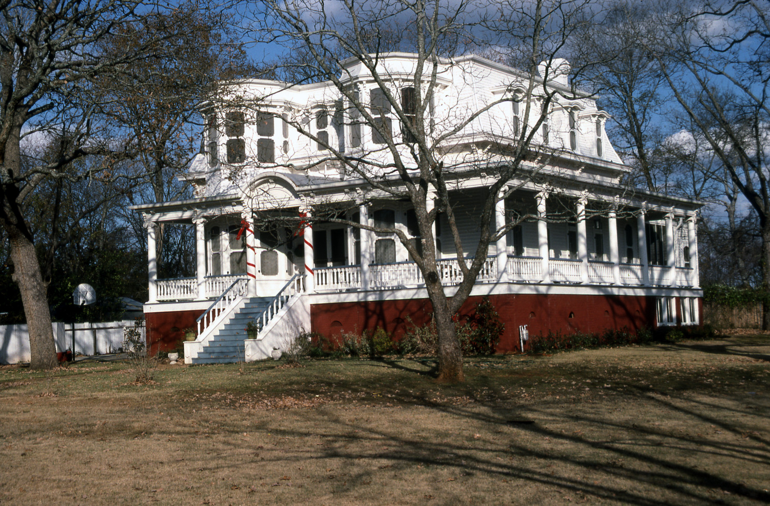 [412 S. Royall], Close-up photograph of the southwest corner of a two-story white house with blue and red accents, located at 416 S. Royall in Palestine, Texas.,