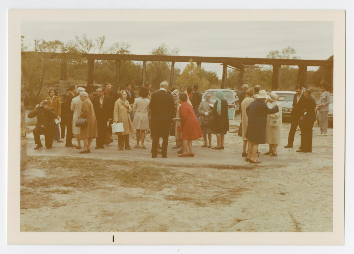 [Group at Dedication of Round Rock Marker], Photograph taken facing west of a group of people gathered around for a historic marker dedication ceremony for Round Rock in Brushy Creek. Cars can be seen behind the group, and a railroad bridge can be seen in the background. A man on the left can be seen kneeling to take a picture of something out of view.,