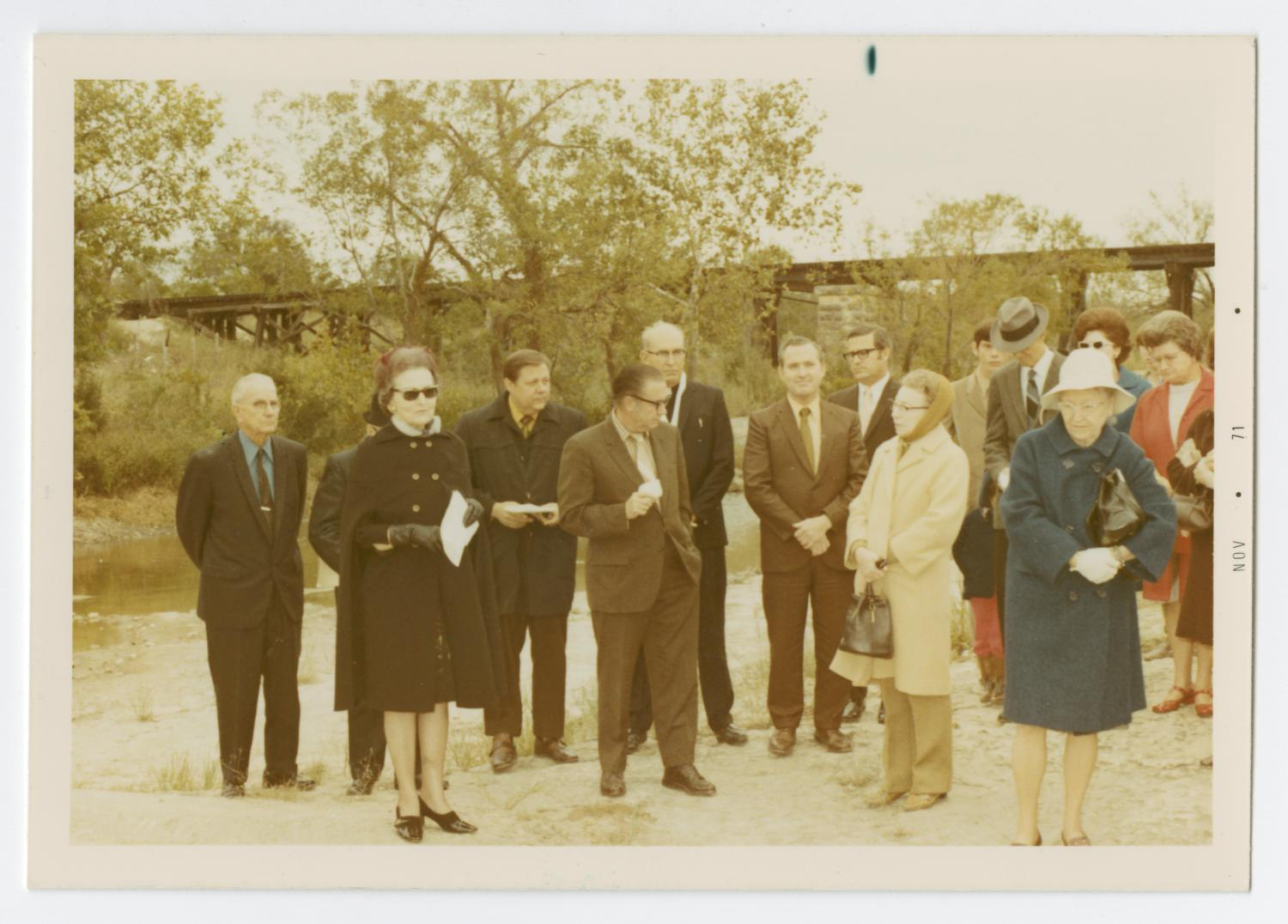 [Group Standing at Round Rock Marker Ceremony], Photograph taken facing west of several individuals gathered for a historic marker dedication ceremony for Round Rock in Brushy Creek.. A woman in sunglasses an cape styled coat can be seen in the left foreground, while a woman in a blue coat and white hat can be seen to the right. A railroad bridge can be seen in the background and a creek can be seen to the left, beyond the group.,