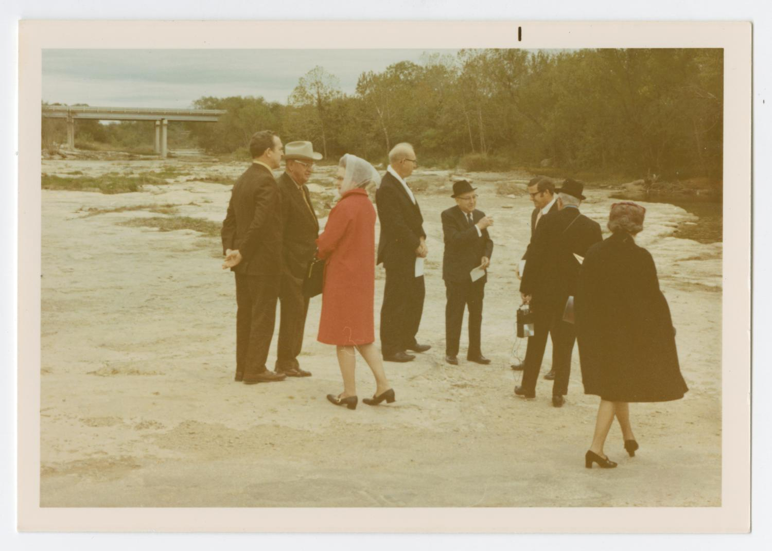 [Photo Taken During Dedication of the Round Rock Marker], Photograph taken facing east of several individuals standing during a historic marker dedication ceremony for Round Rock in Brushy Creek. A highway bridge can be seen in the back ground, and a creek can be seen against a tree line to the far right. A woman stands near the center of the group, seen wearing a bright red coat, and another woman in a black coat can be seen from behind, walking to the right.,