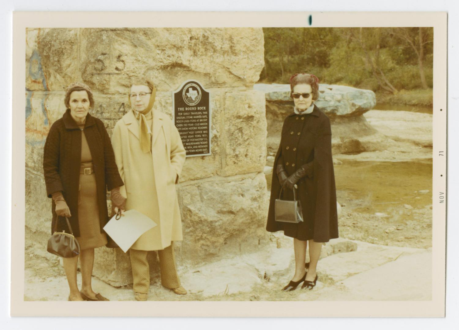 """[Three Women at Round Rock Marker Ceremony], Photograph taken facing east of three women at a historic marker dedication ceremony for Round Rock in Brushy Creek. They can be seen posing with the marker, which is posted on a large stone wall, and are identified on the back of the photo as Mrs. John W. Ledbetter Sr., Mrs. D. B. Gregg, and Mrs. John Cornforth (left to right). In the right background, the """"Round Rock"""" can be seen.,"""