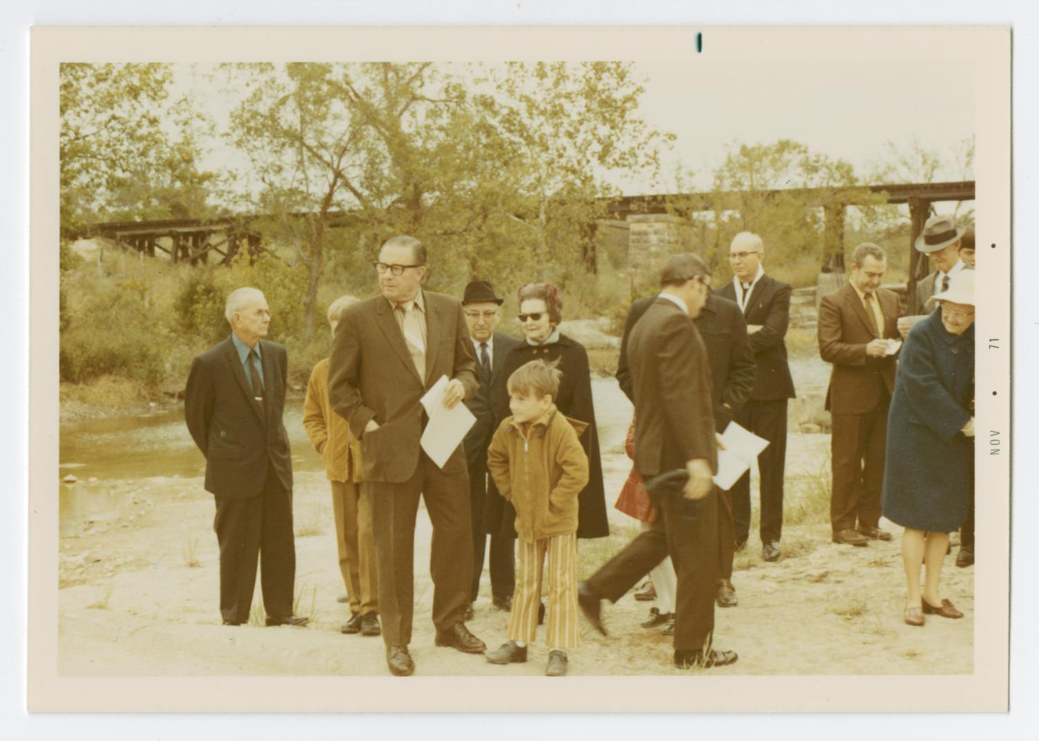 [Dedication of the Round Rock Marker], Photograph taken facing west of a group of individuals gathered around for a historic marker dedication ceremony for Round Rock in Brushy Creek. A boy in striped pants can be seen in the front of the group, standing with his hands in his pockets. A railroad bridge can be seen in the background, and the creek can be seen to left.,