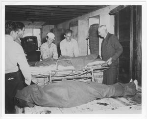 Primary view of object titled '[At the temporary morgue for victims of the 1947 Texas City Disaster]'.
